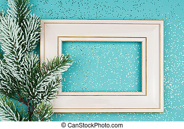 Festive greeting card for Christmas with photo frame, spruce tree branch on blue confetti background.