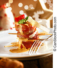 Festive medallions of pork wrapped in bacon on a dish with a beautiful boketh background