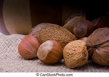 pile of mixed nuts on hessian sacking by wooden bowl.