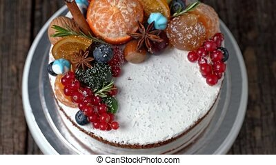 Festive New Years cake decorated with all sorts of fruits spinning on a rotating stand. Closeup