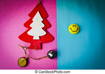 Festive New Year's Christmas winter happy two-tone beautiful joyful background with a small toy wooden homemade tree and a round smiling emoticon. Flat lay. Top view. Holiday decorations