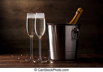 Festive photo of two wine glasses with sparkling wine, iron bucket