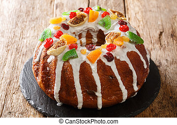 Festive pound cake with raisins, dried apricots, dried cherries, kiwi and cranberries and icing close-up on a board. horizontal