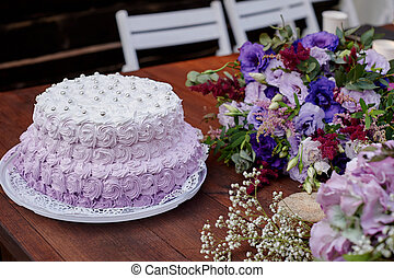 festive wedding cake and a bouquet of flowers on the table