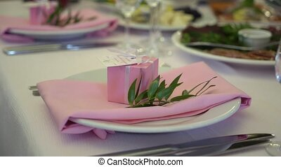Festive wedding table setting with pink flowers, napkins, glasses