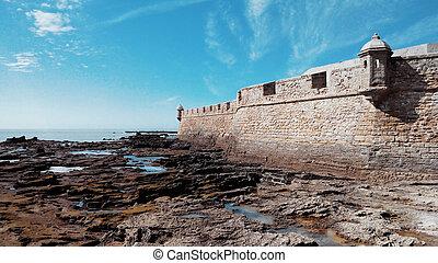 festung, von, san sebastian, niedrigwasser, und, steine, bedeckt, mit, algen, auf, a, sonniger tag, in, cadiz, andalusien, spain.