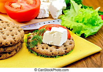 Feta cheese and tomato on a round bread with a knife