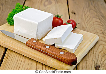 Feta cheese on the board with tomatoes and parsley - Feta...