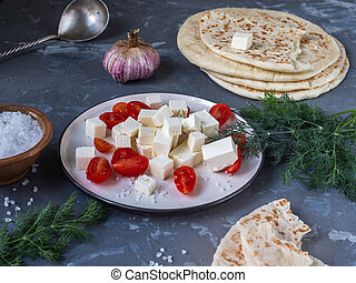 Feta cheese slices with cherry tomatoes, homemade pita for lunch in the background