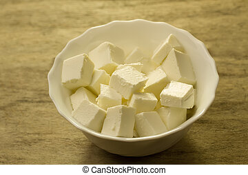 Feta is a traditional Greek cheese on wooden background