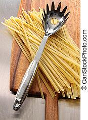 Fettuccine on wooden cutting board - Raw fettuccine on ...