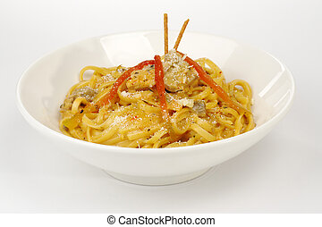 Fettuccine with chicken, mushrooms and red pepper garnished with sticks on white (Selective Focus)