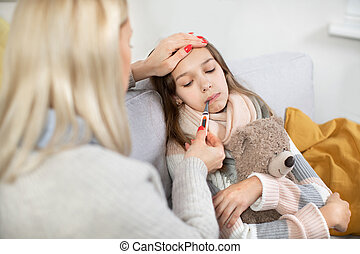 Fever, coronavirus and flu concept. Sick teen girl child with bear toy in bed, with thermometer in her mouth. Back view of blond mother comforting her poor ill girl, checking her temperature