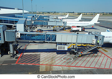 few airliners parked at airport. boarding passengers. service technician