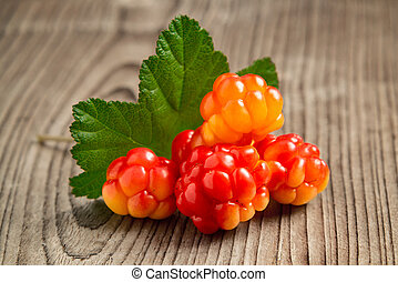 few berries of cloudberries with a leaf on an old wooden board close-up
