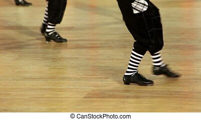 Few boys in shoes dance, only legs are visible