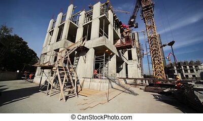 Few builders work around small unfinished edifice, tall...