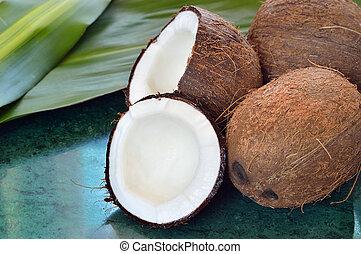 Few coconuts on green marble slab.
