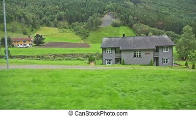 Few country houses among trees at background of moutains,...