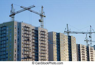 Few cranes crane yellow finish building multi-storey