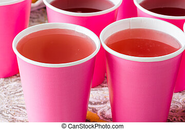 Few cups with two kind of fruit lemonade.