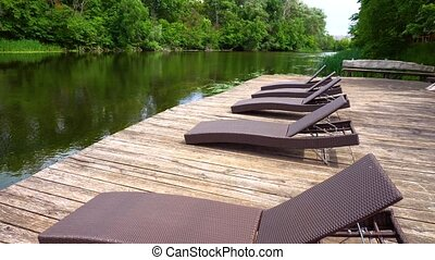 Few loungers standing on wooden pier. Calm river and forest...
