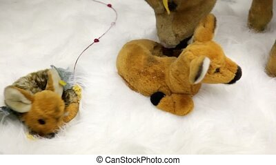 Few moving plush toy animals on artificial snow, elk licking the cub