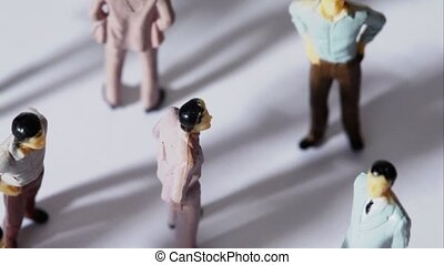 Few painted toy men stand and drop shadows