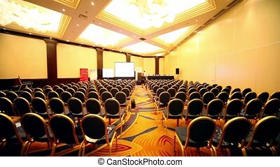 Few people walk in empty conference hall during the break