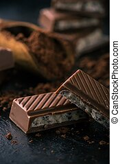 Few pieces of chocolate with creamy filling and cocoa