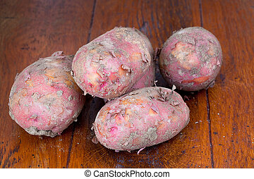 raw pink potatoes on wooden table