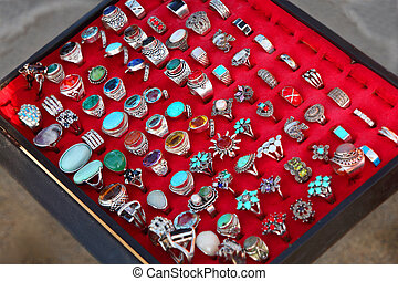 few rows of souvenir large rings on red backing. sale. wide ...