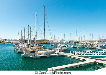 Few yachts in the habror, city background, Spain