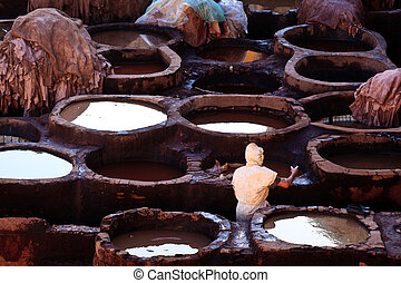 Fez, Morocco: Tanning pools and workers at a traditional leather tannery, Fez Morocco