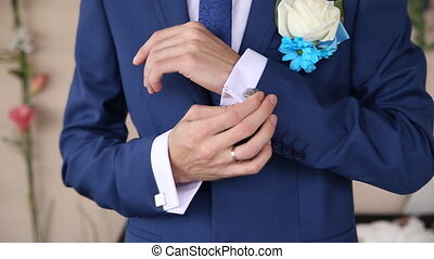 fiance adjusts his gold cufflinks