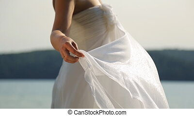 Fiancee in perfect bridal dress stands on berth near water
