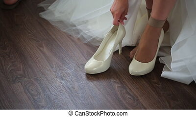 Fiancee puts on pair of white bridal shoes for going out.