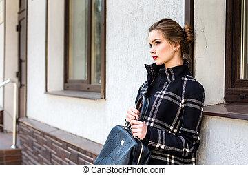 fiatal, gyönyörű woman, noha, egy, elegáns, táska, van, álló, az utcán