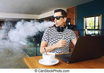 fiatal, jelentékeny, csípőre szabott, ember, insunglasse, ülés, alatt, kávéház, noha, egy, csésze kávécserje, vaping, és, elengedés, egy, felhő, közül, vapor., munka at, laptop, és, birtoklás, egy, kevés, break., noha, másol, space.