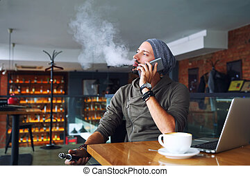 fiatal, jelentékeny, csípőre szabott, ember, noha, szakáll, ülés, alatt, kávéház, noha, egy, csésze kávécserje, vaping, és, elengedés, egy, felhő, közül, vapor., beszéd, mobile telefon, és, birtoklás, egy, kevés, break.