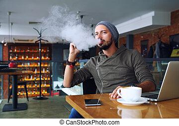 fiatal, jelentékeny, csípőre szabott, ember, noha, szakáll, ülés, alatt, kávéház, noha, egy, csésze kávécserje, vaping, és, elengedés, egy, felhő, közül, vapor., munka at, laptop, és, birtoklás, egy, kevés, break., noha, másol, space.