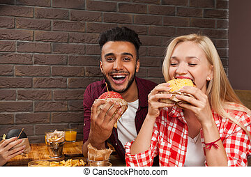 fiatalember, és, woman eszik, gyorsan elkészíthető étel, burgers, ülés, -ban, wooden asztal, alatt, kávéház