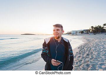fiatalember, noha, fejhallgató, álló, tengerpart, és, mosolygós