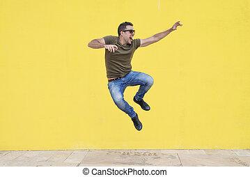 fiatalember, noha, napszemüveg, ugrál, elülső, közül, egy, sárga, wall.