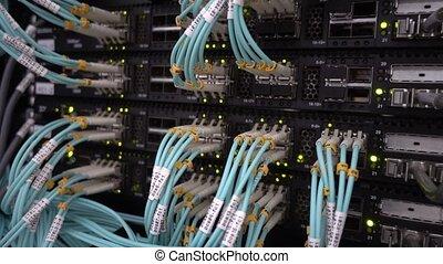 Fiber Optical Cables close up on Datacenter. Telecommunication Broadband. Blink Green Led Lights. Technology server concept