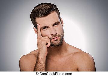 ficar, aproximadamente, pensando, shirtless, cinzento, contra, olhando jovem, solution., enquanto, câmera, fundo, pensativo, retrato, homem