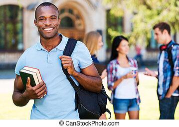 ficar, bonito, seu, fundo, conversando, universidade, jovem, contra, enquanto, livros, segurando, africano, life., sorrindo, desfrutando, amigos, homem