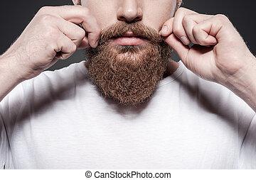 ficar, close-up, próprio, ajustar, jovem, contra, cinzento, barbudo, enquanto, seu, fundo, bigodes, fazer, style., homem