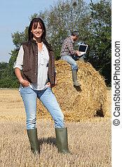 ficar, dela, laptop, agricultor, atraente, em branco, frente, usando, palheiro, senhora, tela, marido, esquerda