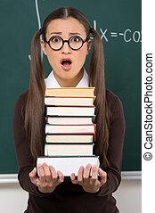 ficar, estudante, quadro-negro, books., jovem, chocado, enquanto, livros, femininas, segurando, frente, pilha, mulheres